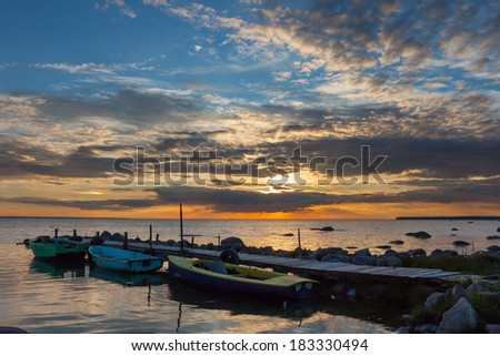 Peaceful sunset with dramatic sky and boats - stock photo