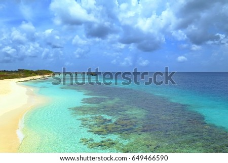 Peaceful tropical sandy empty beach, sea with rich healthy coral reef, sky with dramatic clouds. Sea shore scenery with fine white sandy beach and azure exotic ocean. Paradise vacation island.