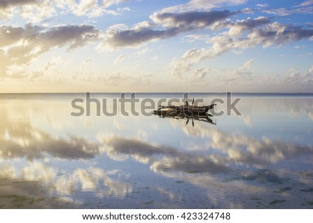 Peaceful waterscape with traditional old vessel called dhow on reflected surface. Tanzania, Zanzibar