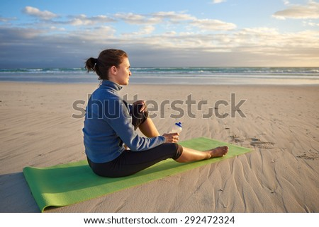 Peaceful woman in sports wear sitting quietly on her yoga-mat on the beach watching the sunrise - stock photo