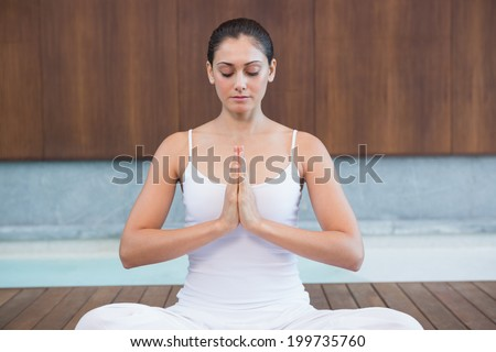 Peaceful woman in white sitting in lotus pose in health spa - stock photo