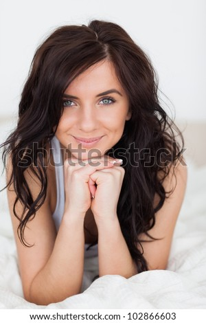 Peaceful woman placing her head on her hands in her bedroom