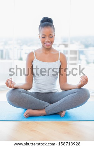 Peaceful woman practicing yoga in bright room at home