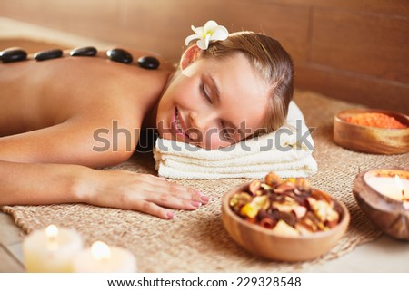 Peaceful woman relaxing in spa salon with her head on folded soft towel and hot stones on her back - stock photo