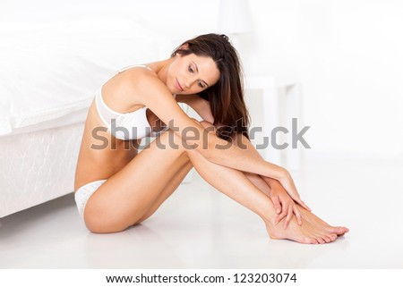 peaceful young woman in underwear sitting on bedroom floor