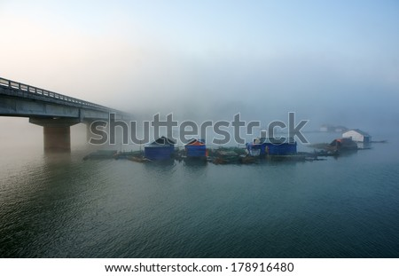Peacefull landscape of fishing village in fog with hamlet have group of house on surface water, big concrete bridge cross the lake, atmosphere full of misty make romantic of Vietnam country