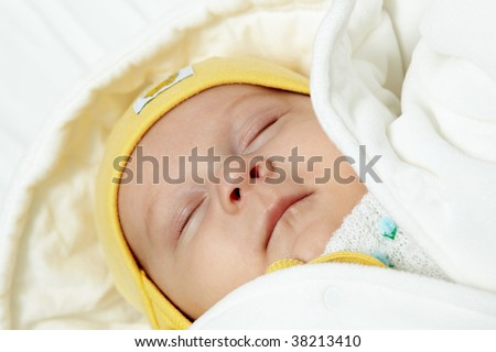 Peacefully sleeping baby dressed in white.