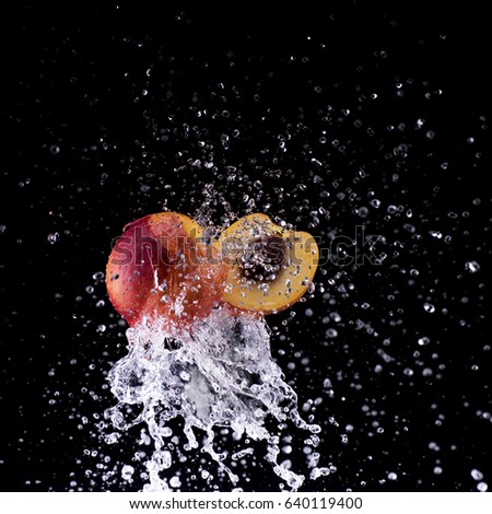 peach and half in water splash on back background