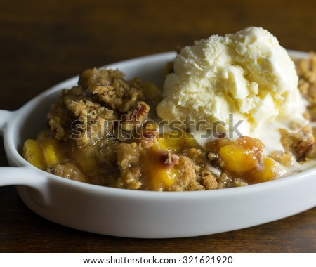 Peach and pecan cobbler with a scoop of ice cream.  - stock photo