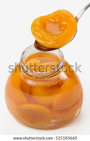 Peach compote in jar and on spoon - stock photo