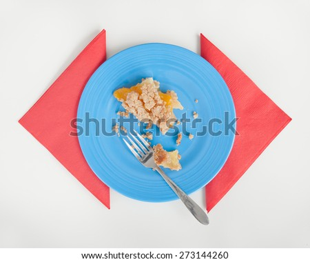 Peach Crumble pie leftovers on blue plate with red napkins. White table surface. - stock photo