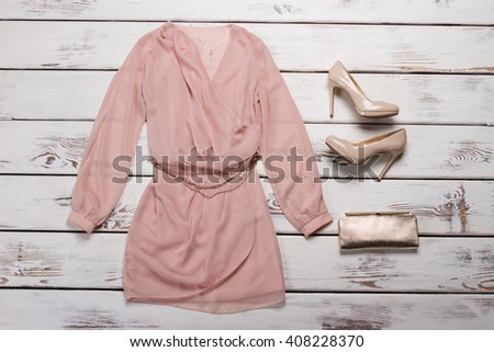 Peach dress and red heels. Evening apparel on wooden showcase. Woman's outfit with glossy heels. Huge discounts for clothing. - stock photo