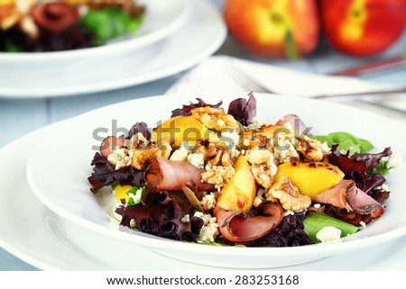 Peach, Gorgonzola And Pastrami Salad with a balsamic vinaigrette. Extreme shallow depth of field with selective on salad in foreground.  - stock photo