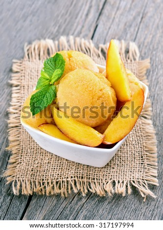 Peach ice cream with mint in white bowl on rustic table - stock photo