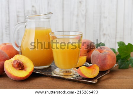 Peach juice in jug and glass with fresh peaches on wooden background