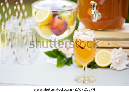 Peach lemonade in a glass on the outdoor party drink station - stock photo