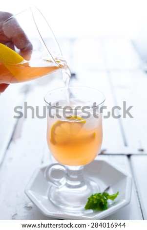 Peach Lemonade Pouring from the Jar into the glass with Ice cubes, lemon wedges and Mint Sprigs - stock photo
