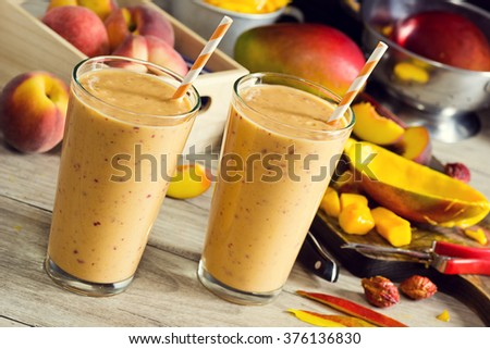 Peach Mango Smoothies or Milkshakes in Glasses with Ingredients on Wooden Table - stock photo
