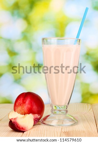 Peach milk shake on wooden table on bright background