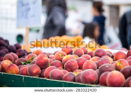 Peaches and apricots in bins at a farmer's market.  Shoppers out of focus in the background. - stock photo