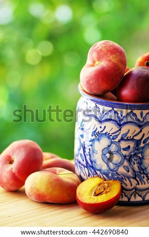 Peaches and nectarines in ceramic  pot - stock photo