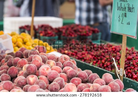 Peaches, cherries and oranges stacked in bins at a farmer's market in San Francisco.  Man out of focus in the background in a blue and white plaid shirt.  Sign with price in the right foreground. - stock photo