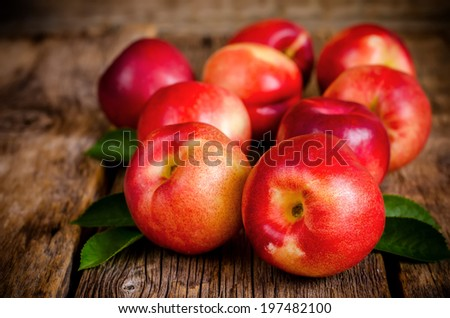 peaches on a dark wood background. toning. selective focus on right peach. - stock photo