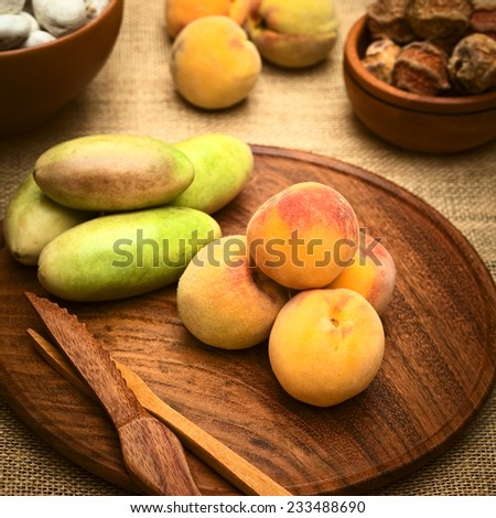 Peaches on round wooden plate with banana passionfruit (lat. Passiflora tripartita) next to it, photographed with natural light (Selective Focus, Focus on the front of the peaches) - stock photo