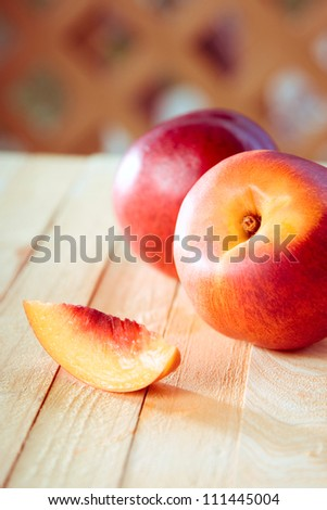 peaches with a slice of a peach on a wooden table - stock photo