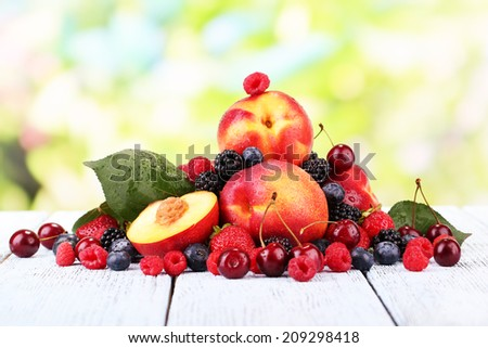 Peaches with berries on table on natural background