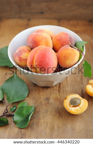 Peaches with leaves in bowl on rustic wooden table