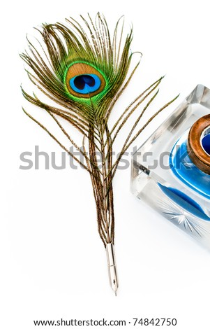 Peacock feather quill and inkwell isolated on white - stock photo