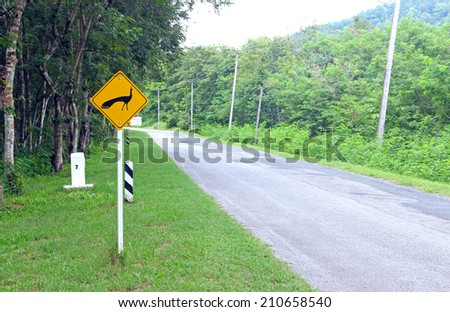 Peacock traffic sign with asphalt road - stock photo