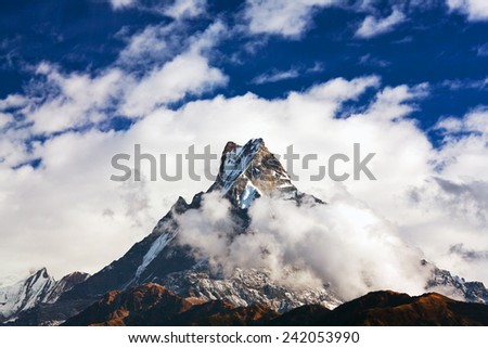 Peak Machapuchare over clouds. Machapuchare or Machhaphuchhare is a mountain in the Annapurna Himal of north central Nepal - stock photo