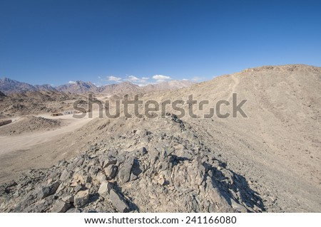 Peak of rocky mountain in arid desert landscape against blue sky background - stock photo