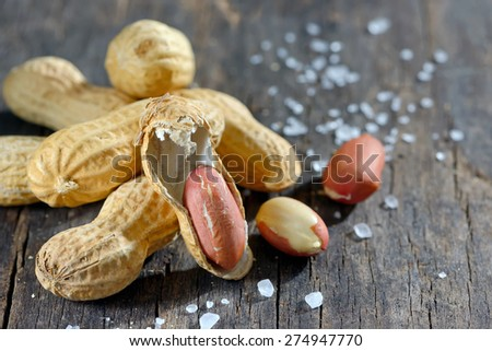 peanut and salt on wooden background - stock photo