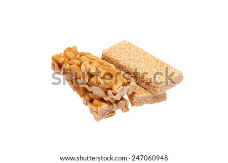 Peanut brittle with sesame seeds and peanuts. Isolated on white.                                - stock photo