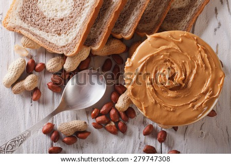 Peanut butter and bread on the table close-up. horizontal view from above  - stock photo