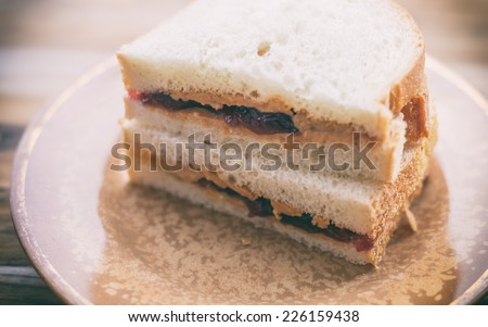 Peanut butter and grape jelly sandwich on white bread, cut in half on a small rustic plate against a wooden cutting board.  - stock photo