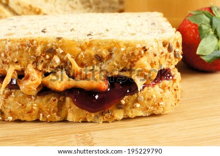 Peanut butter and jelly sandwich close up on wooden background - stock photo