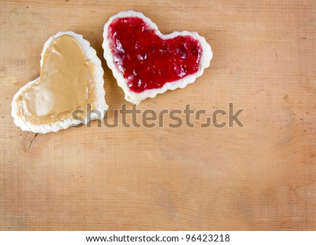 Peanut butter and jelly sandwich cut in a heart shape on a wooden board - stock photo