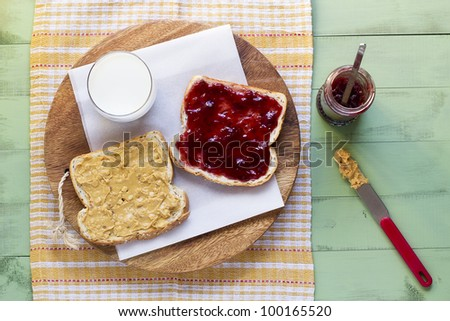 peanut butter and jelly sandwich with glass of milk, overhead perspective - stock photo