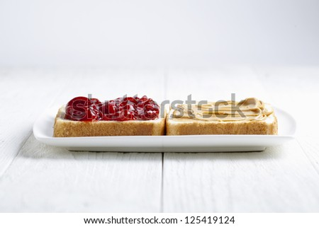 Peanut butter and strawberry jam sandwich on a white plate - stock photo