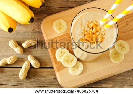 Peanut butter banana oat smoothie with paper straws, on a wood board on rustic table, downward view - stock photo