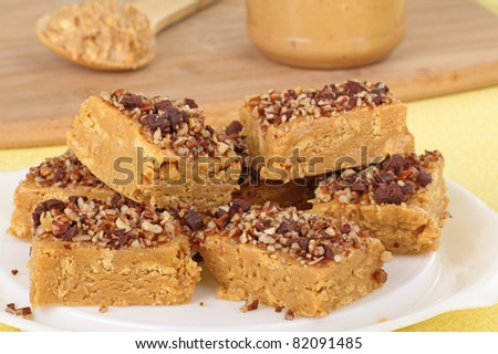 Peanut butter bars topped with nuts and chocolate