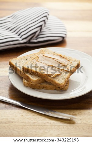 Peanut butter breads with knife on wooden background. focused on bread