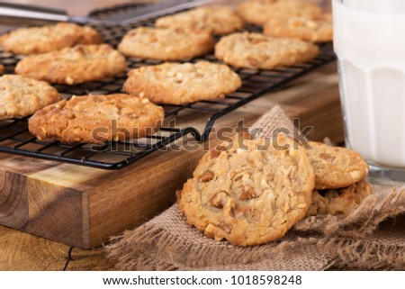 Peanut butter cookies on a burlap cloth with cookies on a cooling rack and glass of milk in background
