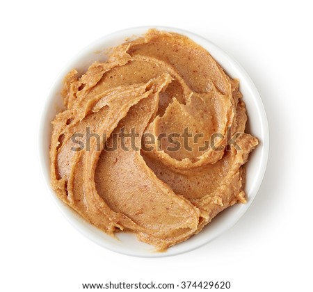 Peanut butter in round dish isolated on white background, top view - stock photo