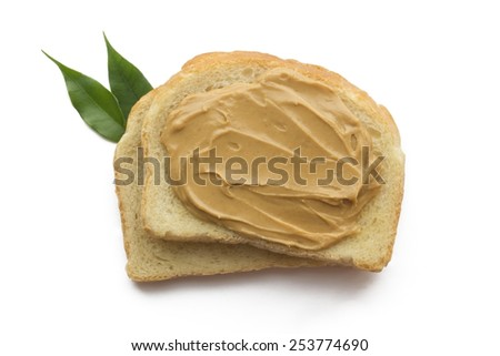Peanut butter sandwich on each other isolated with green leaf. - stock photo