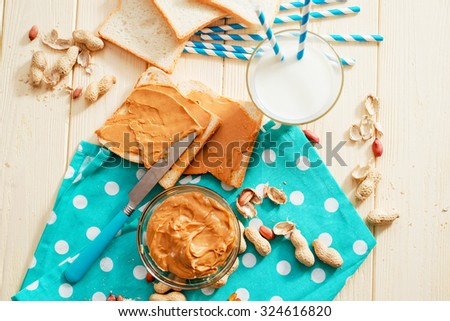 peanut butter sandwich with milk and peanuts on the wooden background
